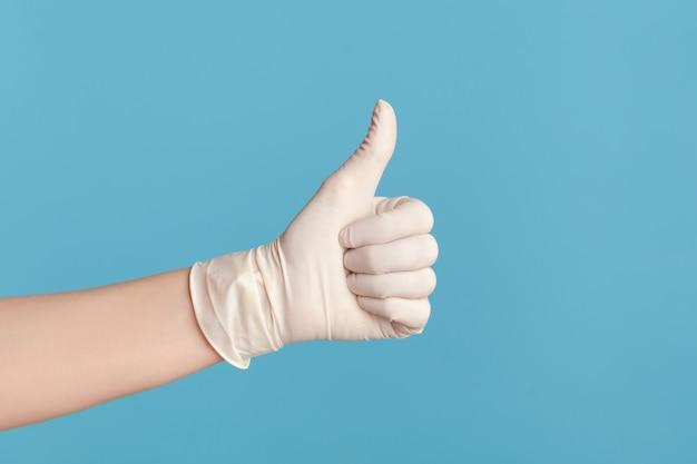 프로필 측면 보기 흰색 수술 장갑에 인간의 손의 근접 촬영 좋아하거나 엄지손가락을 보여줍니다.