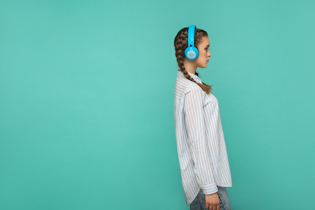 Profile side view of girl in striped blue shirt and pigtail hairstyle, standing listening music with headphone and looking away with serious face, indoor studio shot, isolated on green background