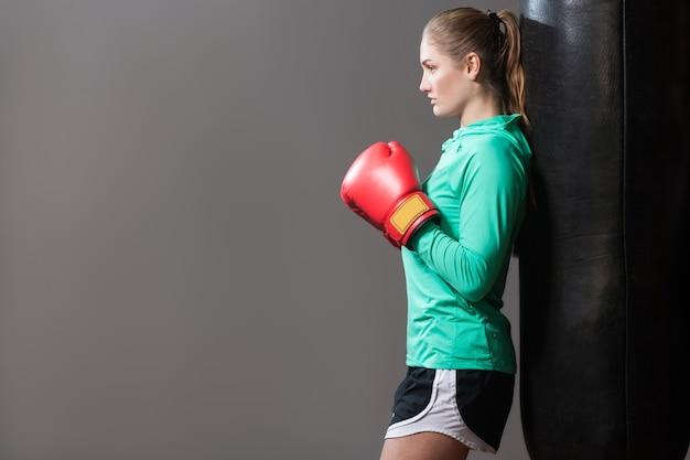 緑の長袖とボクシングの赤い手袋のサンドバッグに寄りかかって黒のショートパンツで収集された髪を持つ深刻な若いアスリートの女性のプロファイル側面図。屋内、濃い灰色の背景に分離