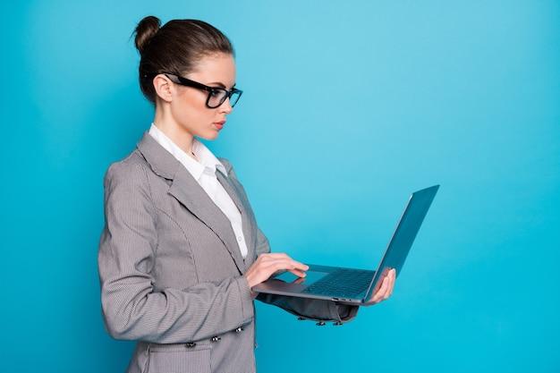 Вид сбоку профиля привлекательной сосредоточенной занятой леди, держащей в руке с помощью ноутбука, изолированной на ярко-синем цветном фоне