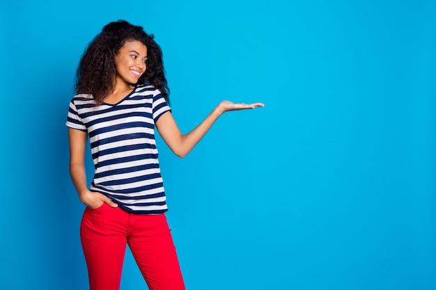 何か、製品のプレゼンテーション、青い壁のコピースペースを保持している陽気なアフロアメリカ人女性プロモーターのプロファイル側面図