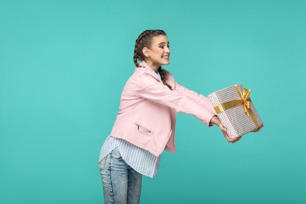 Вид сбоку в профиль счастливой красивой девушки в повседневном стиле, прическа с косичкой и розовой курткой, стоящая и дающая пунктирную подарочную коробку с зубастой улыбкой, студийный снимок, изолированный на синем или зеленом фоне