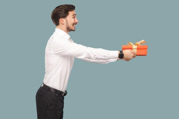 Вид сбоку профиля счастливого смайлика бородатого человека в белой рубашке, стоящего и держащего красную подарочную коробку, дающего и смотрящего в сторону с зубастой улыбкой. крытый, студийный снимок, изолированные на светло-синем фоне