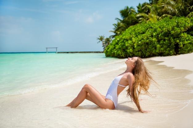 Профиль ее вид сбоку она красивая привлекательная изящная стройная длинноволосая девушка модель сидит на пляже позирует, наслаждаясь солнечный жаркий день прозрачный аква приморский свежий воздух