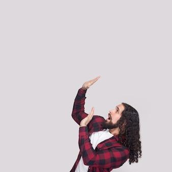 수염과 검은색 긴 곱슬머리를 한 겁에 질린 남자의 옆모습은 캐주얼한 체크무늬 빨간 셔츠를 입고 서서 두려운 충격을 받은 얼굴로 올려다보고 있습니다. 실내 스튜디오 촬영, 회색 배경에 고립.