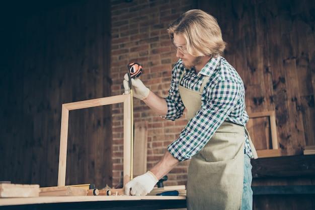 彼のウッドショップでポーズをとって真面目なひげを生やした職人の縦断側面図