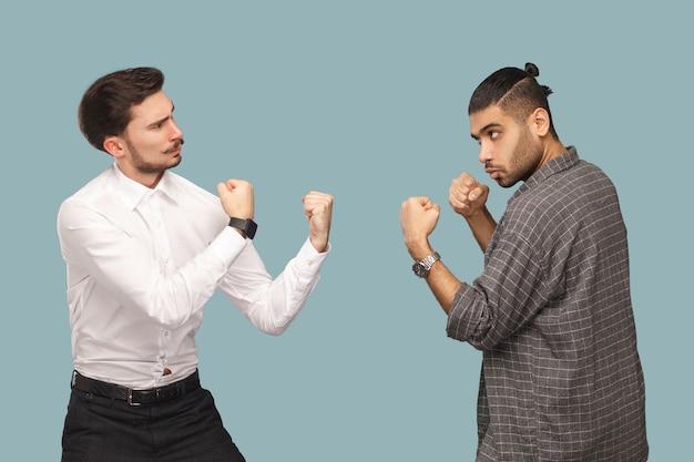 두 명의 화난 권투 선수 사업가의 프로필 측면에서 진지한 얼굴로 서로를 바라보고 공격할 준비가 되어 있습니다. 위기와 파트너십 문제. 밝은 파란색 배경에 고립 된 실내 스튜디오 촬영.