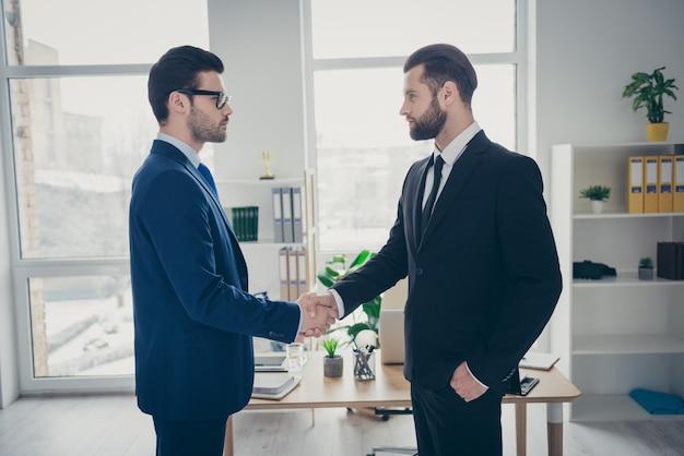 Вид сбоку в профиль двух симпатичных привлекательных модных представительных мужчин, квалифицированных финансовых экспертов, работодателей, обменивающихся рукопожатием, нанимающих талантливых человеческих ресурсов на светло-белой внутренней рабочей станции