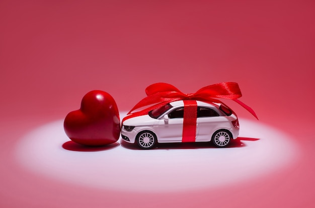 Profile side view photo of modern stylish toy beautiful white present gift car with little red heart standing in center of spotlight searchlight isolated on red background copy-space