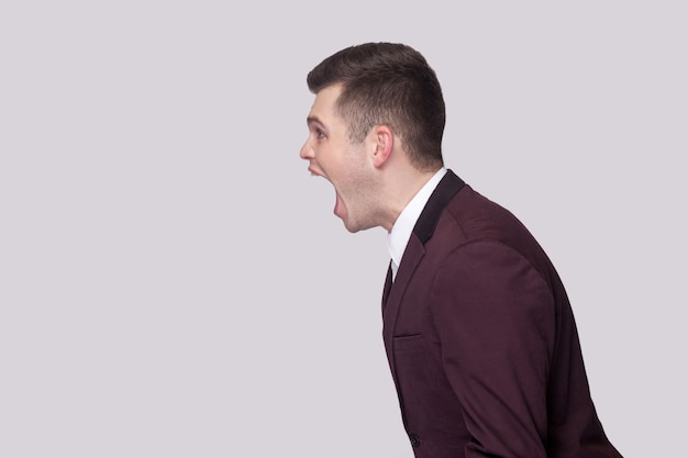 Профиль вида сбоку портрет агрессивного красивого молодого человека в фиолетовом костюме и белой рубашке, стоящего и кричащего с нервным лицом. крытая студия выстрел, изолированные на сером фоне.