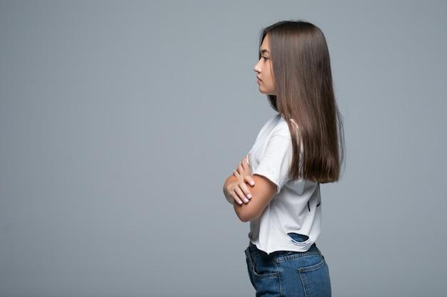 Profili il ritratto di vista laterale del colpo dell'interno dello studio della giovane donna asiatica, isolato su fondo grigio chiaro.