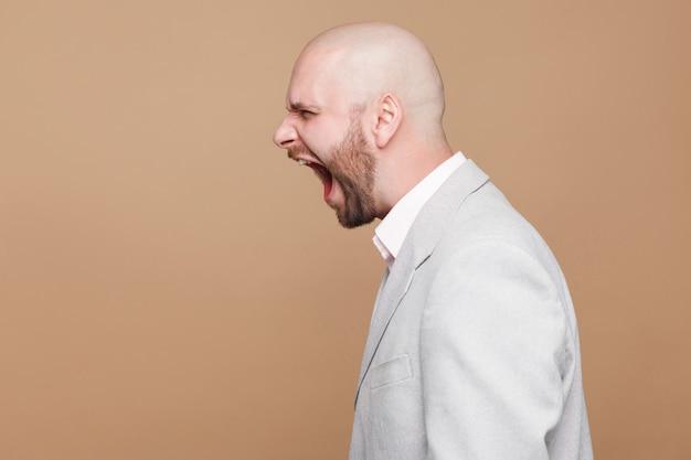 Профиль вид сбоку портрет сумасшедший гнев лысого бородатого бизнесмена средних лет в светло-сером костюме, стоящего и кричащего с oepn ртом. крытая студия выстрел, изолированные на светло-коричневом фоне.