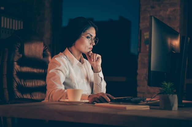 Profile side view portrait of her she nice attractive focused lady economist auditor attorney lawyer top manager company owner marking analysis deadline at night dark work place station indoors