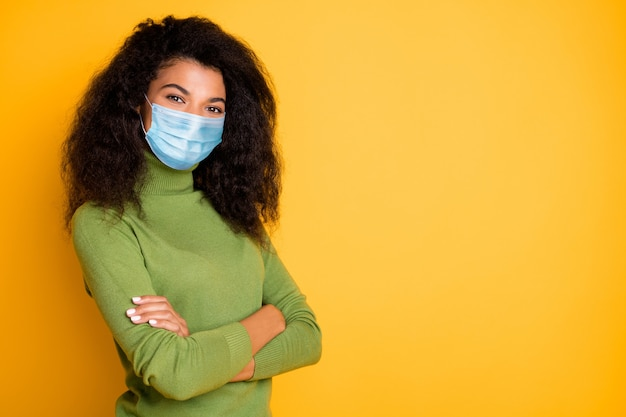 Profile side view portrait of her she nice attractive wavy-haired girl folded arms wearing safety mask mers cov prevention china wuhan pandemia empty space isolated vibrant yellow color background
