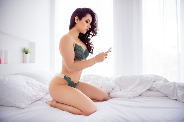 Profile side view portrait of her she nice fit slim sporty attractive lovable girl sitting on bed using device sending photos to boyfriend chatting in light white interior house apartment