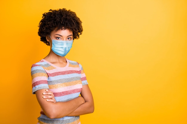 Profile side view portrait of her she nice healthy wavy-haired girl nurse wearing safety gauze mask folded arms mers cov prevention isolated bright vivid shine vibrant yellow color background