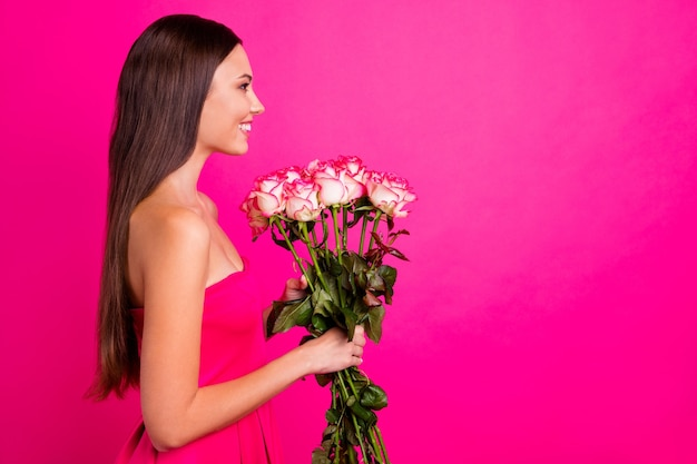 Profile side view portrait of her she nice-looking attractive lovely cheerful cheery long-haired girl holding in hands cute bouquet isolated on bright vivid shine vibrant pink fuchsia color background