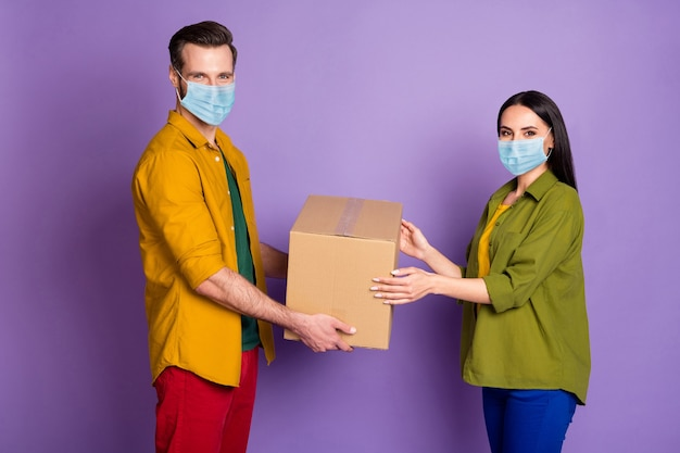 Profile side view portrait of his he her she nice attractive couple wearing safety gauze mask guy delivering order drop ship health care stop pandemia mers cov isolated violet purple color background