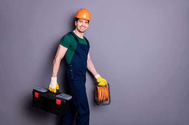 Profile side view portrait of his he nice attractive cheerful professional qualified workman walking renovation service carrying instruments isolated over gray pastel color wall