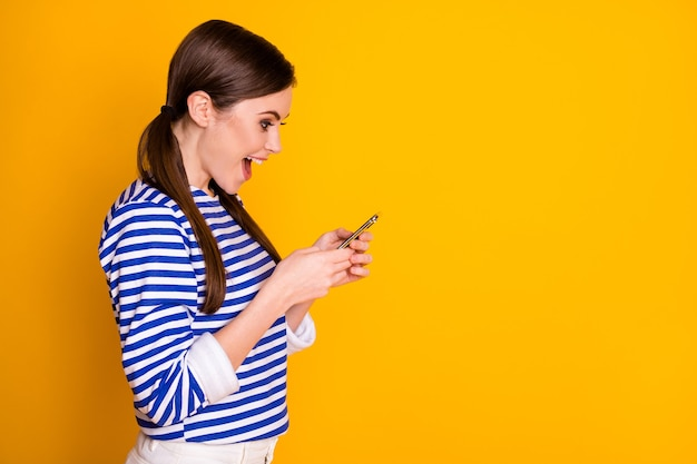 Profile side view portrait of nice attractive pretty amazed glad cheerful cheery brown-haired girl using device app 5g fast speed connection isolated bright vivid shine vibrant yellow color background