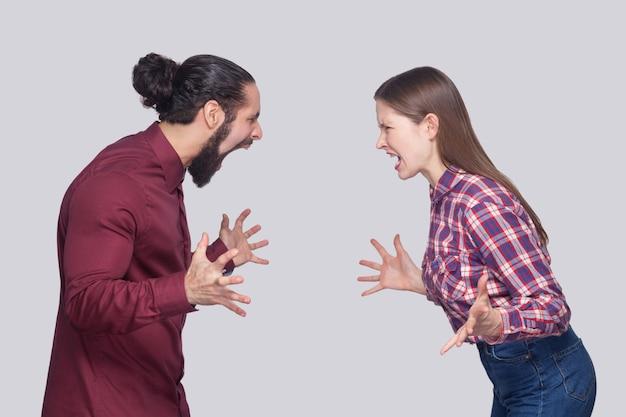 옆모습은 검은색 머리를 묶은 화난 수염난 남자와 캐주얼한 스타일의 여성이 서서 서로를 바라보고 소리를 지르는 모습을 보여줍니다. 실내 스튜디오 촬영, 회색 배경에 고립.