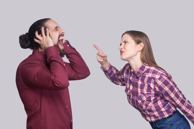 검은 머리를 가진 불행한 남자를 비명을 지르며 서서 비난하는 화난 여성의 프로필 측면 초상화. 실내 스튜디오 촬영, 회색 배경에 고립.