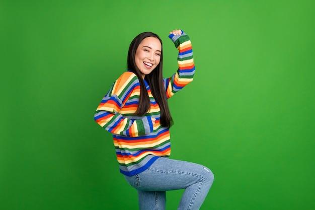 明るい緑色の背景に分離された楽しみを持って踊っている魅力的な陽気な女の子の縦断的な側面図の肖像画