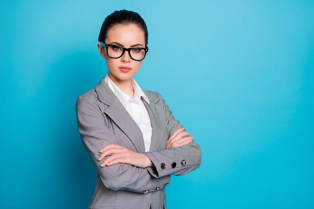 明るい青色の背景の上に分離された魅力的なコンテンツ上品なスマートな女性の腕を組んだの縦断側面図の肖像画