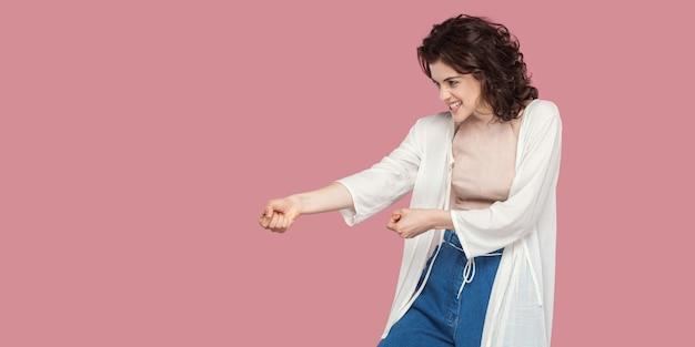 주먹으로 서 있는 캐주얼 스타일의 곱슬머리 헤어스타일을 한 아름다운 브루네트 젊은 여성의 프로필 측면 초상화, 공격하거나 몸짓을 당기려고 합니다. 분홍색 배경에 격리된 실내 스튜디오 샷입니다.