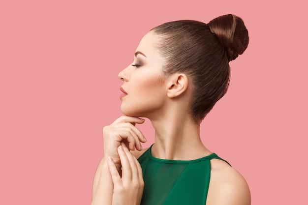 Профиль вида сбоку портрет спокойной серьезной красивой молодой женщины с прической и макияжем булочки в зеленом платье, стоя с закрытыми глазами и касаясь ее подбородка. студия выстрел, изолированные на розовом фоне.