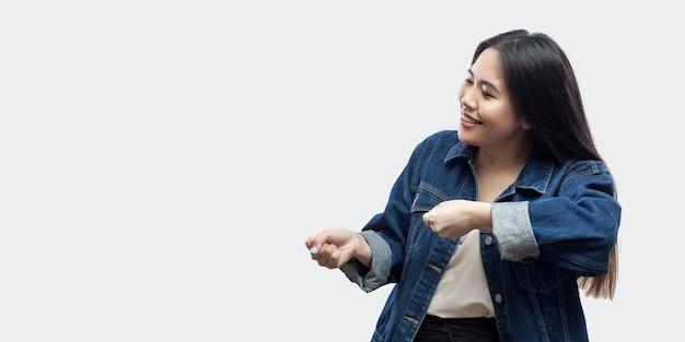 옆모습은 화장을 하고 서 있는 캐주얼한 파란색 재킷을 입은 우스꽝스러운 아름다운 브루네트 아시아 젊은 여성의 초상화를 보여주고 몸짓을 보여주려고 합니다. 스튜디오 촬영, 밝은 회색 배경에 고립.