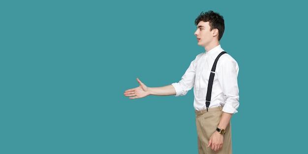 Профиль вид сбоку портрет счастливого красивого кудрявого молодого бизнесмена в классической повседневной белой рубашке стоя и протягивая руку приветствию или рукопожатию. крытая студия выстрел, изолированные на синем фоне.