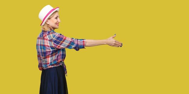 Профиль вид сбоку портрет счастливой современной стильной зрелой женщины в непринужденном стиле с шляпой стоя, глядя с зубастой улыбкой, протягивая руку приветствию. крытая студия выстрел, изолированные на желтом фоне.