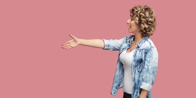 Профиль вид сбоку портрет счастливой молодой кудрявой женщины в повседневной голубой рубашке, стоящей, с нетерпением жду и протягивающей руку приветствию или рукопожатию и зубастой улыбке. студийный снимок на розовом фоне