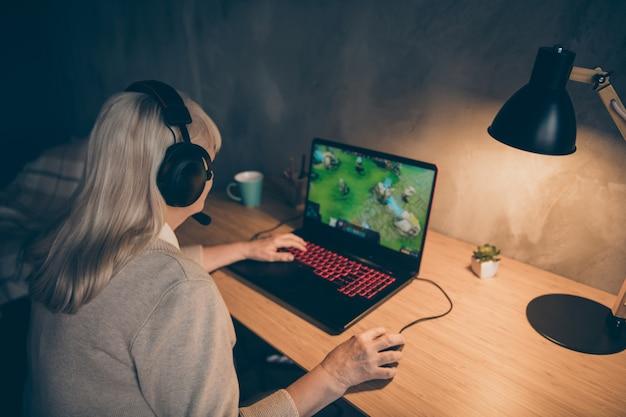 Профиль, вид сбоку, ее портрет, она красивая, привлекательная, сосредоточенная, седая, блондинка, бабушка, играет в сетевую виртуальную командную игру на промышленном чердаке, современный бетонный стиль