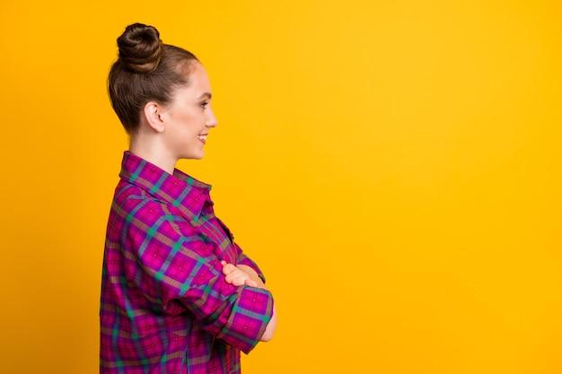 彼女のプロフィール側面図肖像画彼女の素敵な魅力的な陽気なコンテンツ女の子フリーランサーチェックシャツ腕を組んでコピー空の空白スペース孤立した明るい鮮やかな輝き鮮やかな黄色の背景