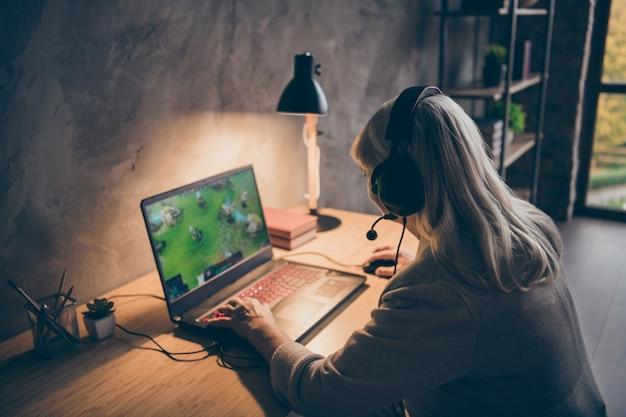 Профиль, вид сбоку, портрет, ее симпатичная, привлекательная, сосредоточенная седая блондинка, бабушка, играющая в удаленную командную онлайн-игру на пк на промышленном чердаке, современный интерьер в бетонном стиле, квартира в помещении