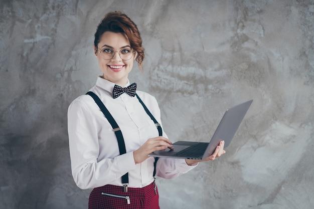 그녀의 프로필 측면 초상화 회색 콘크리트 산업 벽 배경에서 격리된 원격으로 자체 개발 작업을 하는 랩톱을 사용하는 밝고 쾌활한 물결 모양의 머리 소녀