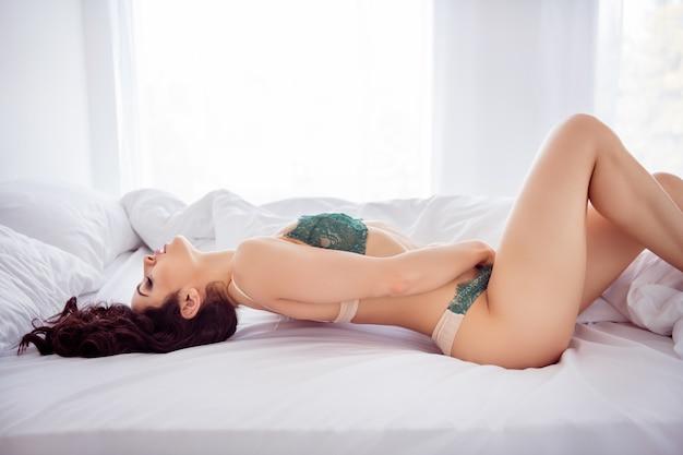 그녀의 프로필 측면 초상화 그녀는 날씬하고 스포티하고 날씬한 슬림하고 사랑스러운 아름다운 소녀가 밝은 흰색 인테리어 룸 하우스 아파트에서 즐기는 침대에 누워 자신을 애무하고 있습니다.