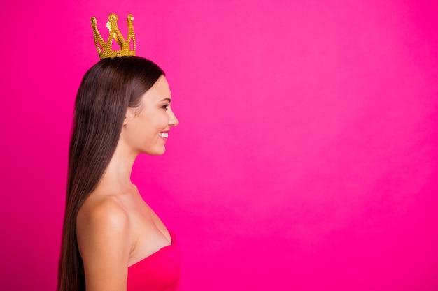 Профиль, вид сбоку, портрет ее красивой привлекательной, красивой, ухоженной, веселой, жизнерадостной, длинноволосой девушки в короне, изолированной на ярком ярком сиянии, ярком розовом цветном фоне фуксии.