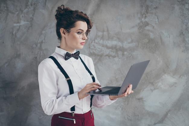 회색 콘크리트 산업 벽 배경에서 원격으로 작업하는 디지털 노트북을 사용하는 그녀의 멋지게 보이는 매력적인 사랑스러운 콘텐츠에 초점을 맞춘 물결 모양의 머리 소녀의 프로필 측면 초상화