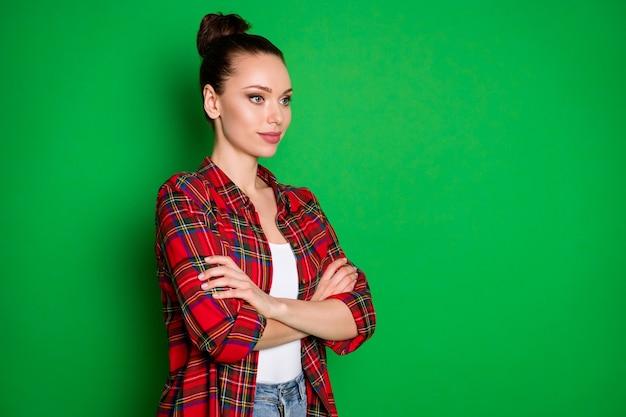 明るい鮮やかな輝きの鮮やかな緑色の背景に分離されたチェックの赤いシャツの腕を組んで彼女の見栄えの良い魅力的なかわいいかわいい陽気な女の子の縦断側面図の肖像画