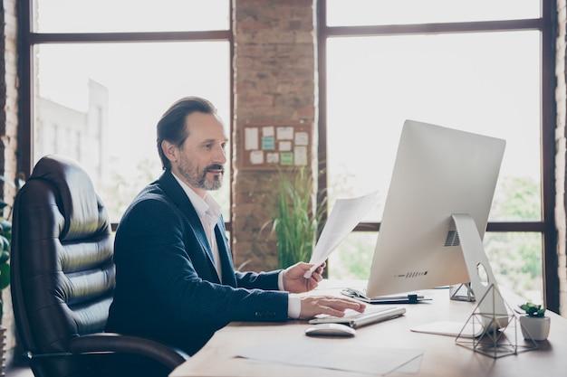 현대 로프트 벽돌 산업 오픈 스페이스 작업장에서 재무 계획 보고서를 입력하는 그의 잘생긴 바쁜 집중된 쾌활한 남자 고용주 전문가의 프로필 측면 초상화