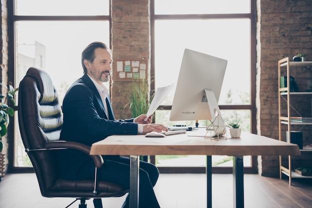 그의 잘생긴 바쁜 남자 자격을 갖춘 경제학자 금융 전문가의 프로필 측면 초상화 현대 로프트 벽돌 산업 열린 공간 작업 장소 역에서 계획 보고서 판매 산업을 준비
