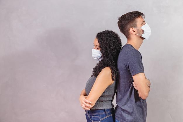 그의 프로필 측면보기 초상화 그녀는 그녀가 아프고 건강에 좋지 않은 건강에 좋지 않은 커플 접힌 팔을 입고 안전 거즈 마스크를 착용했습니다.
