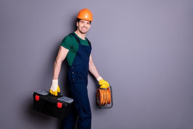 Профиль, вид сбоку, портрет его он красивый привлекательный веселый профессиональный квалифицированный рабочий, идущий по ремонту, неся инструменты, изолированные на серой пастельной стене