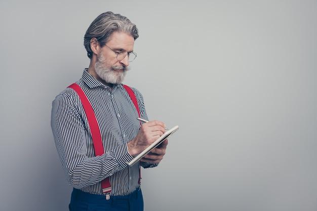 회색 파스텔 컬러 배경 위에 절연 일정을 계획하는 메모를 작성하는 그의 좋은 매력적인 유행 잘 차려 입은 집중된 남자의 프로필 측면보기 초상화