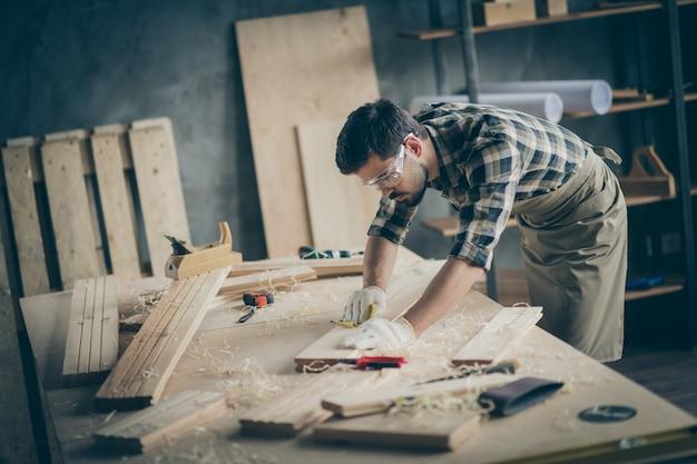 Профиль, вид сбоку, портрет его симпатичного привлекательного, квалифицированного, опытного трудолюбивого парня, самозанятого строителя, резьба по дереву на столе в современном промышленном интерьере в стиле лофт в кирпичном помещении