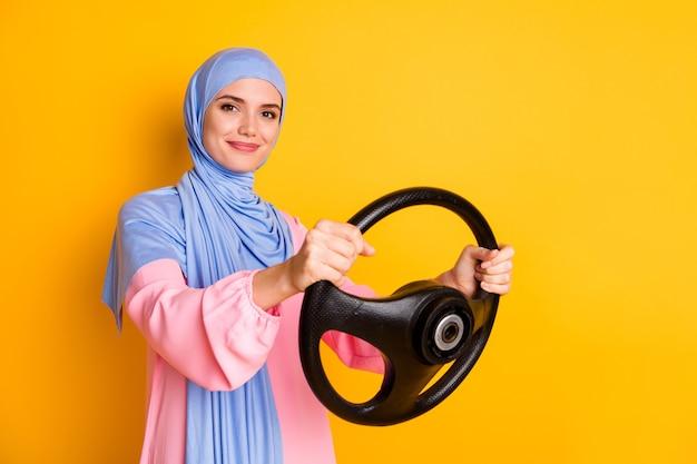 밝은 노란색 배경에 격리된 보이지 않는 차를 운전하는 히잡을 쓴 멋진 콘텐츠 전문적인 쾌활한 이슬람교도의 프로필 측면 초상화