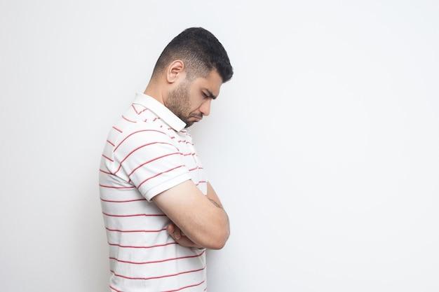 悲しい一人の横顔の肖像画o落ち込んでいるひげを生やした若い男の縞模様のtシャツを着て立って、頭を下げて気分が悪いか考えている。白い背景で隔離の屋内スタジオショット。